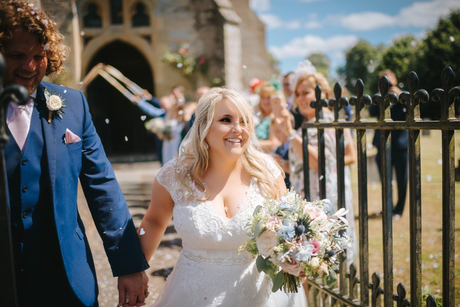 Smiling bride with pastel coloured bouquet