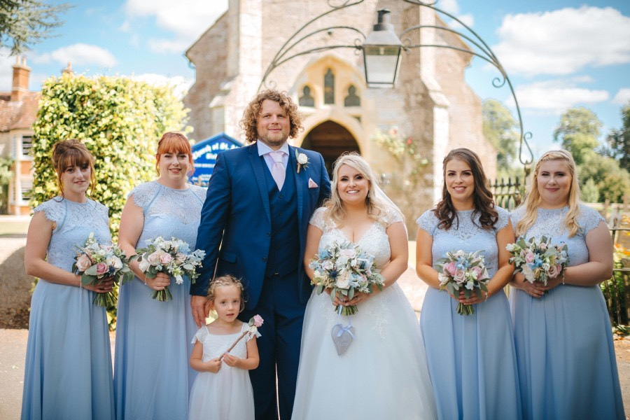 bride and groom with bridesmaids and flower girl in pale blue and ivory