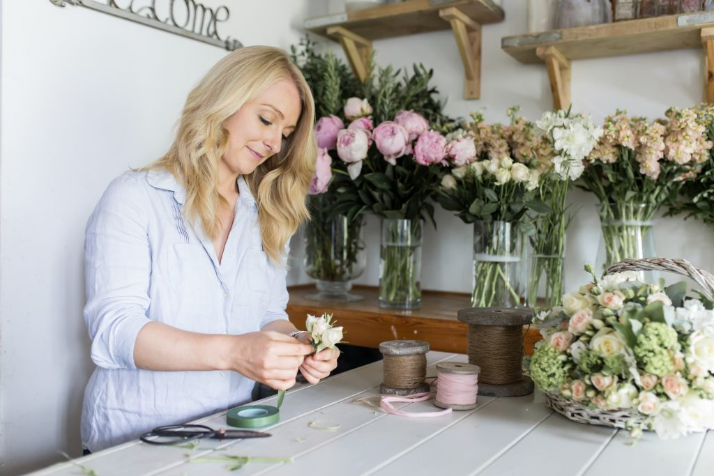 daisy lane floral design florist making a buttonhole surrounded by flowers