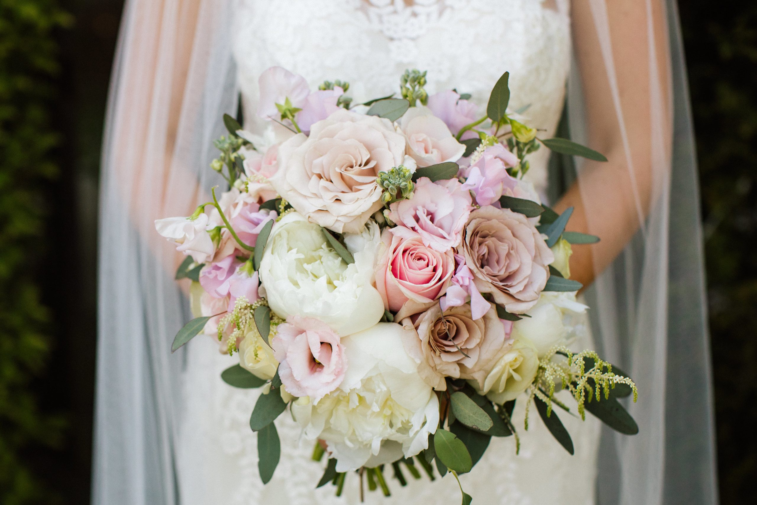bride holding handtied wedding bouquet with pink and ivory flowers