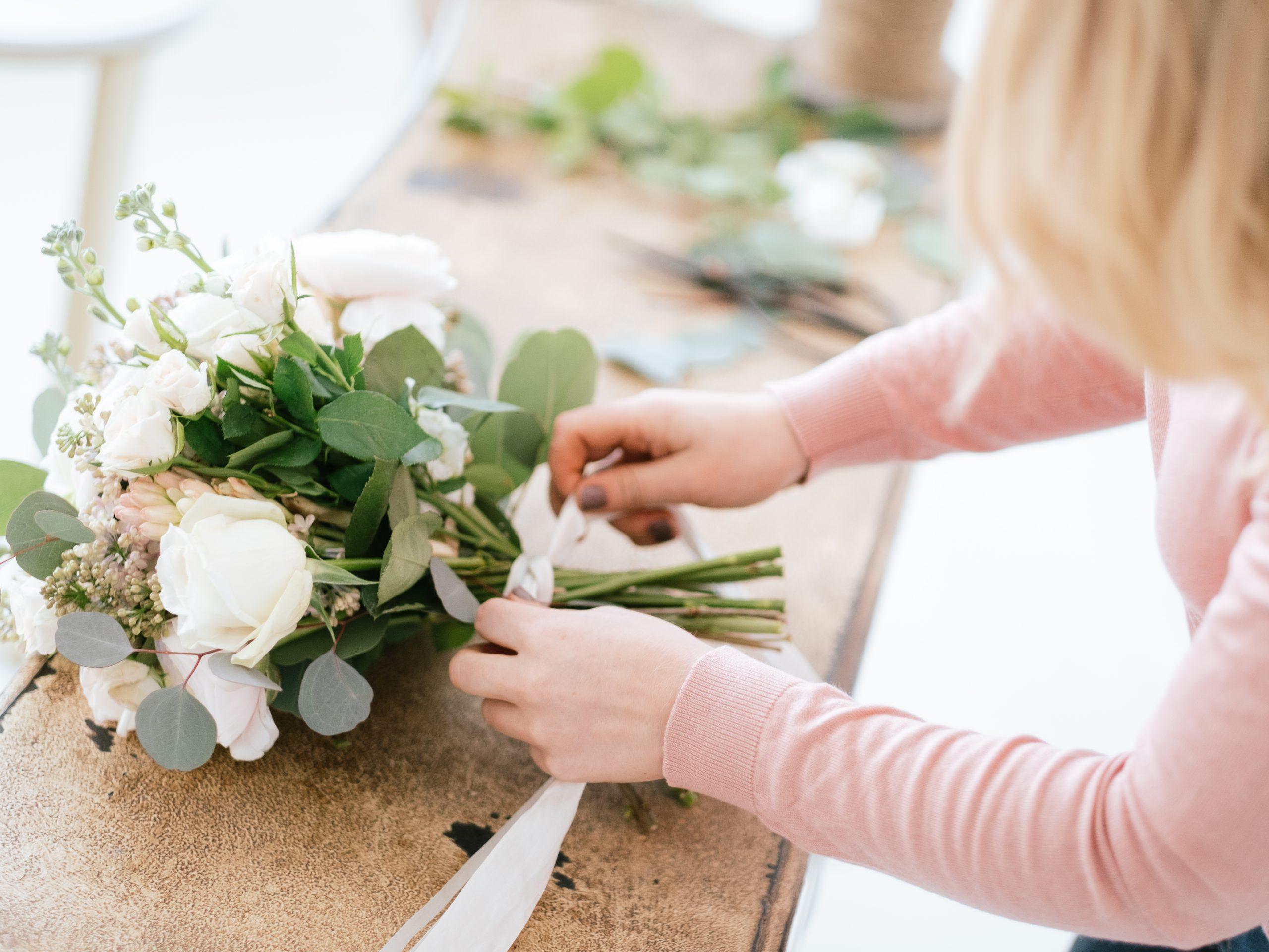 Daisy lane floral design florist tying ribbon around wedding bouquet