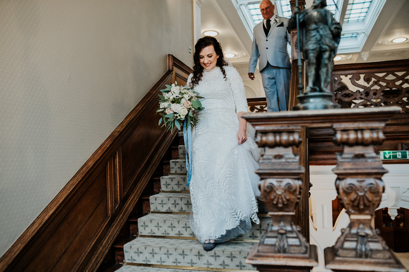 bride descending staircase with wedding bouquet at Clevedon Hall North Somerset wedding venue