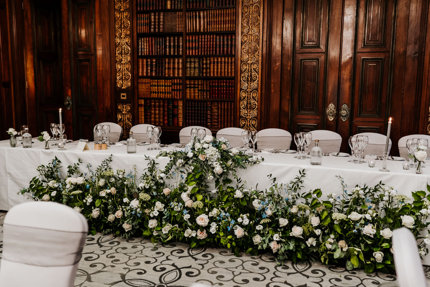 Daisy Lane Floral Design meadow arrangements in front of top table at wedding breakfast Clevedon Hall