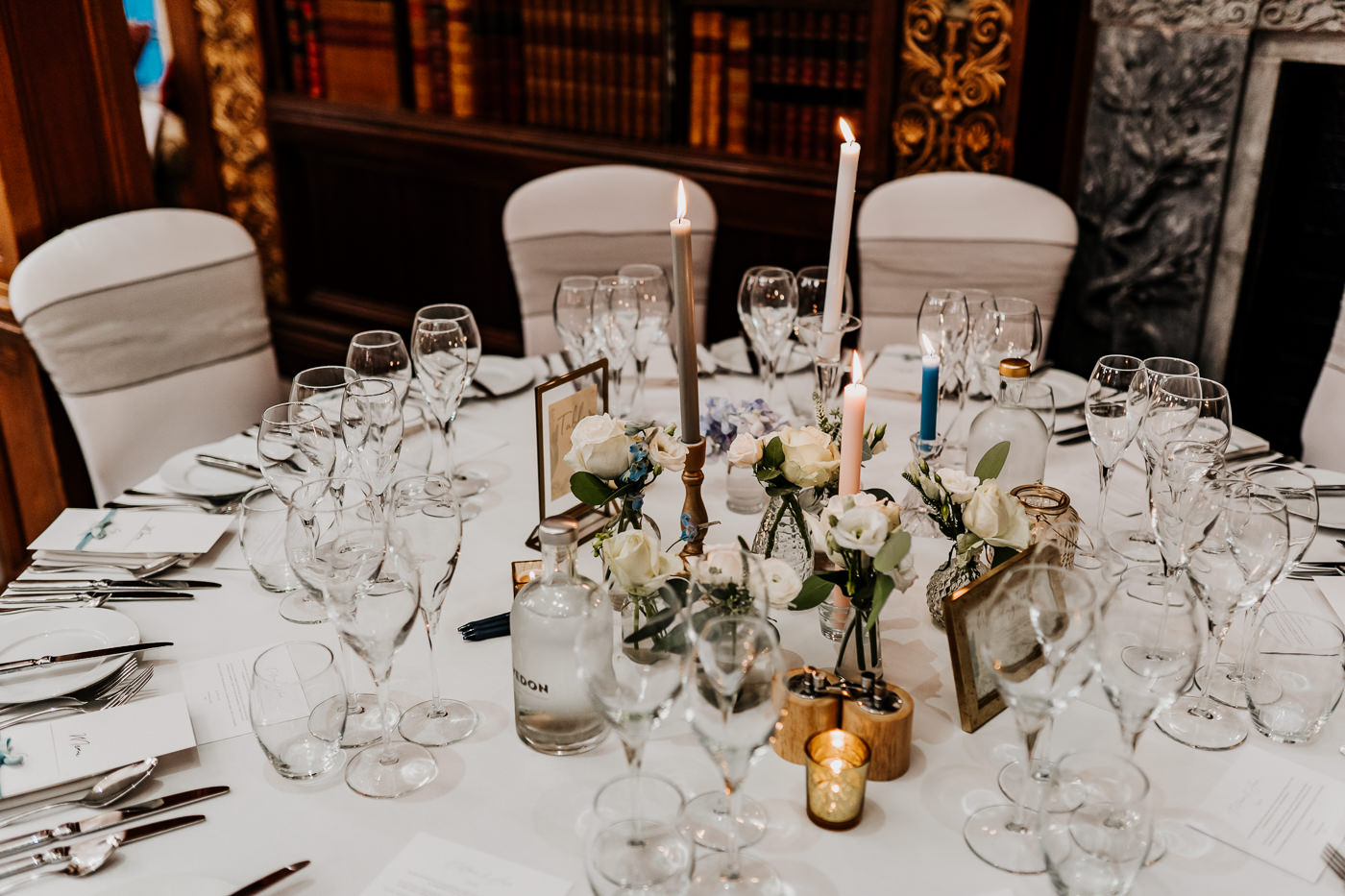 guest tables decorated with cut glass jars, flowers and candles