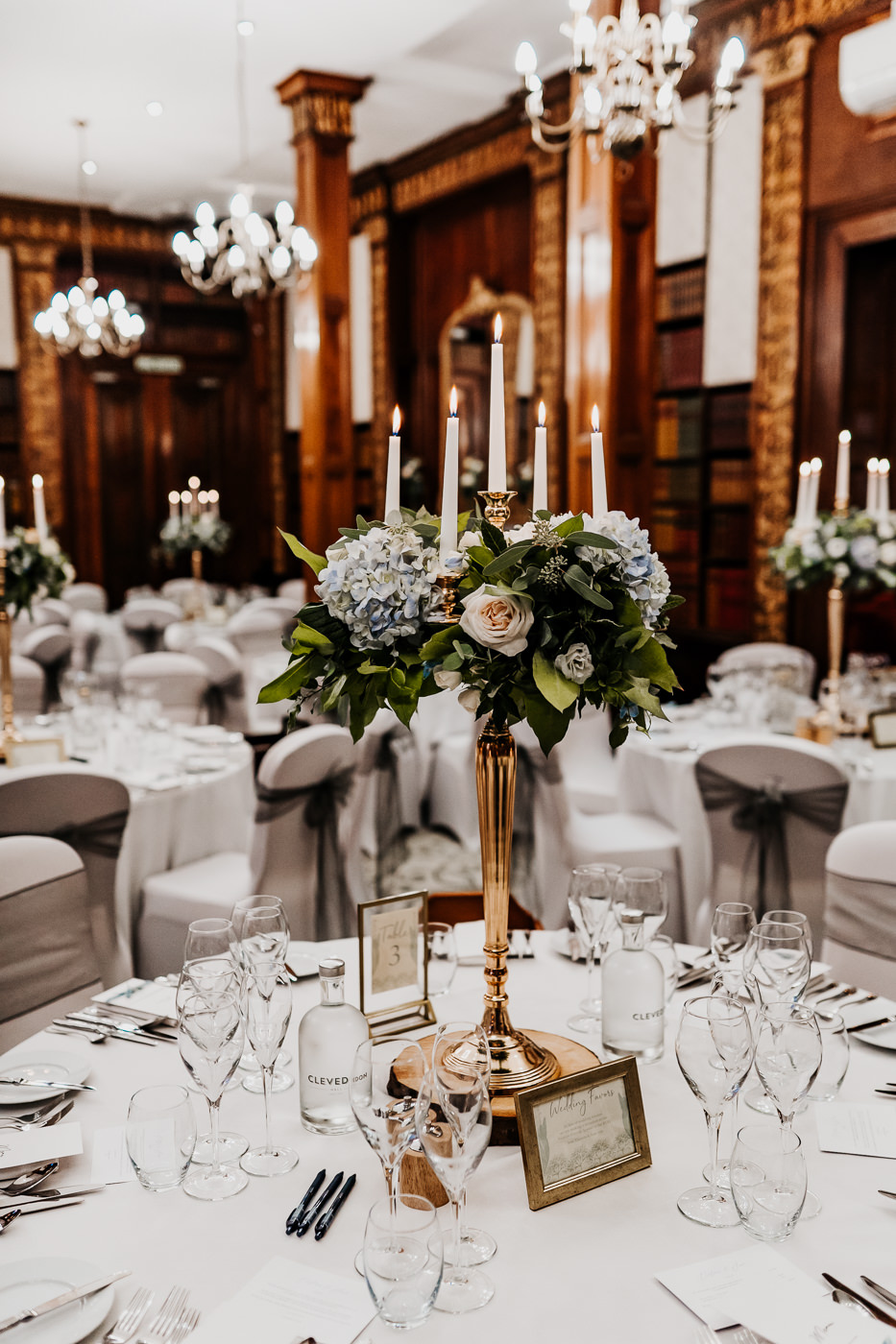 wedding breakfast reception floral arrangements on tall gold candelabras