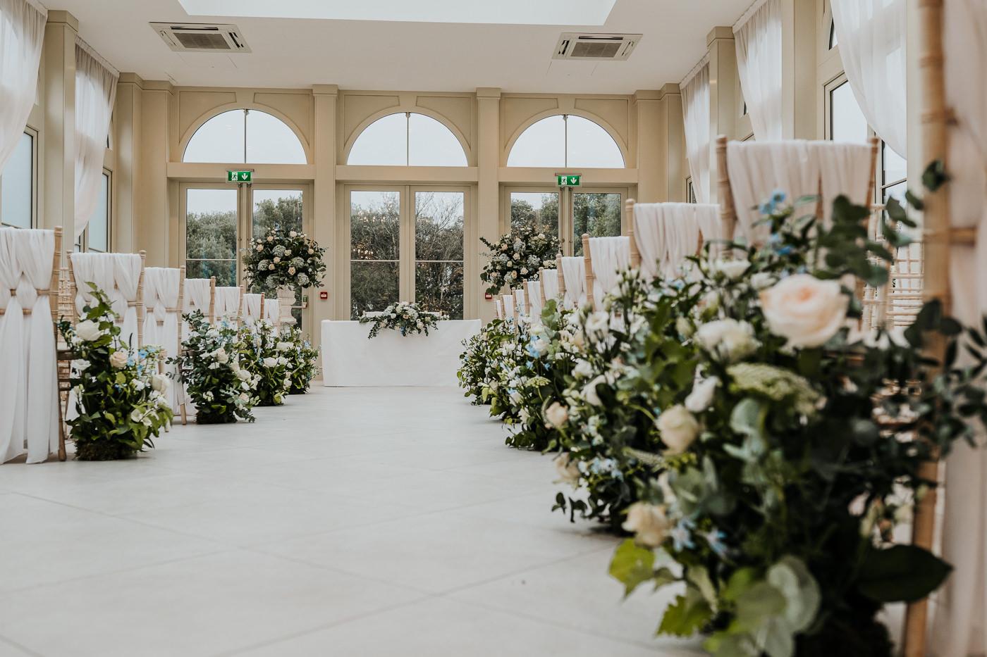 Vertical meadow arrangements lining ceremony aisle