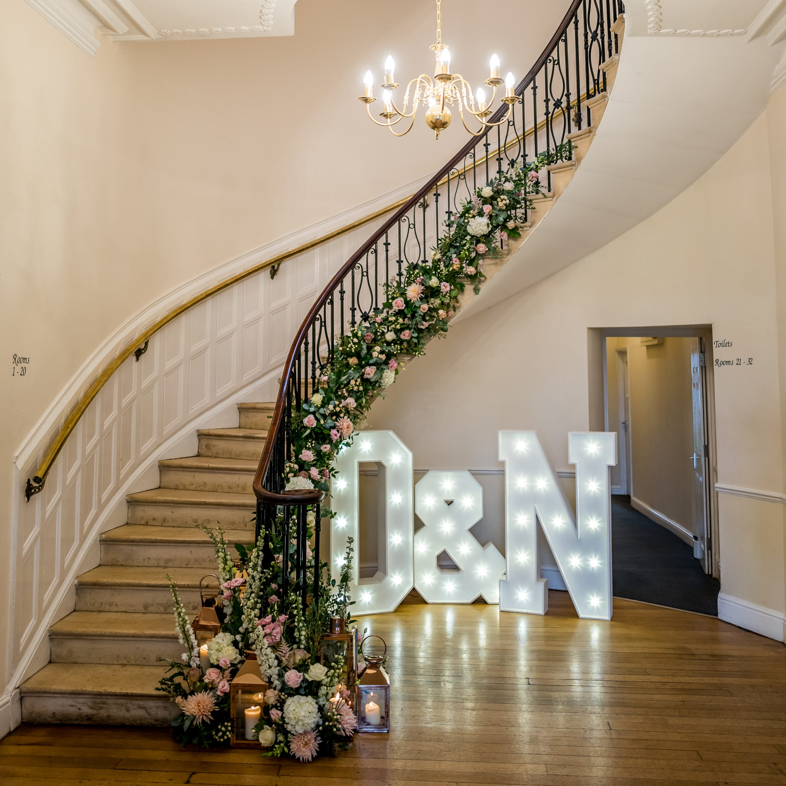 wedding flowers at eastington park staircase decorated with flowers large light-up letters