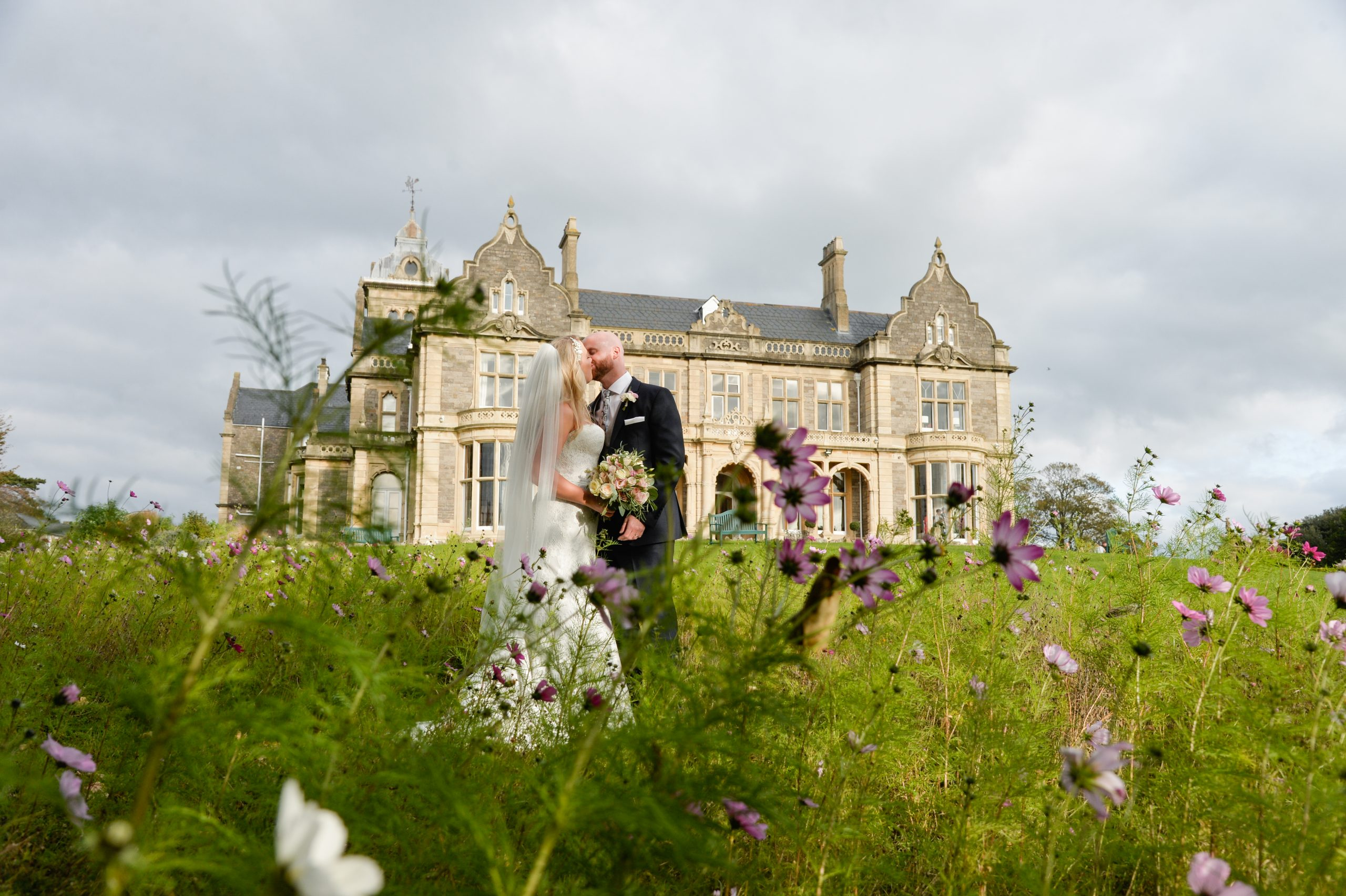 bride and groom kissing among wild flowers at Clevedon Hall