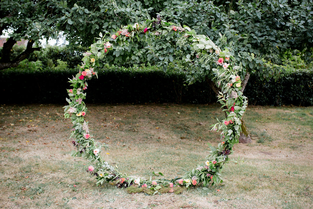 Floral moon gate for outdoor wedding ceremony