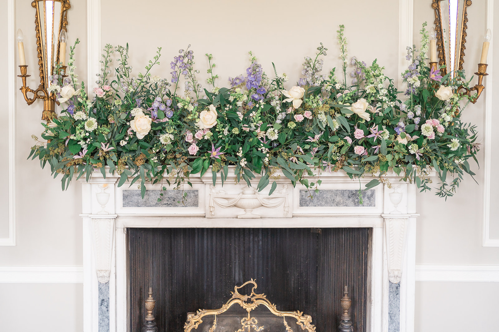 floral installation above fireplace at wedding ceremony