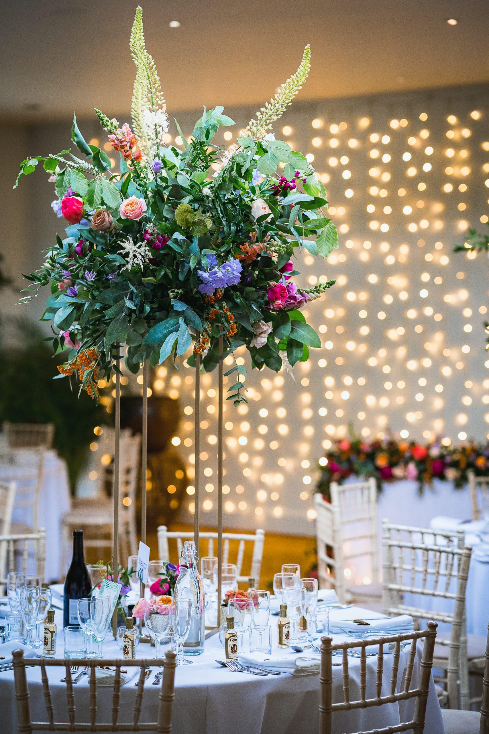 tall riser wedding flowers against fair lights
