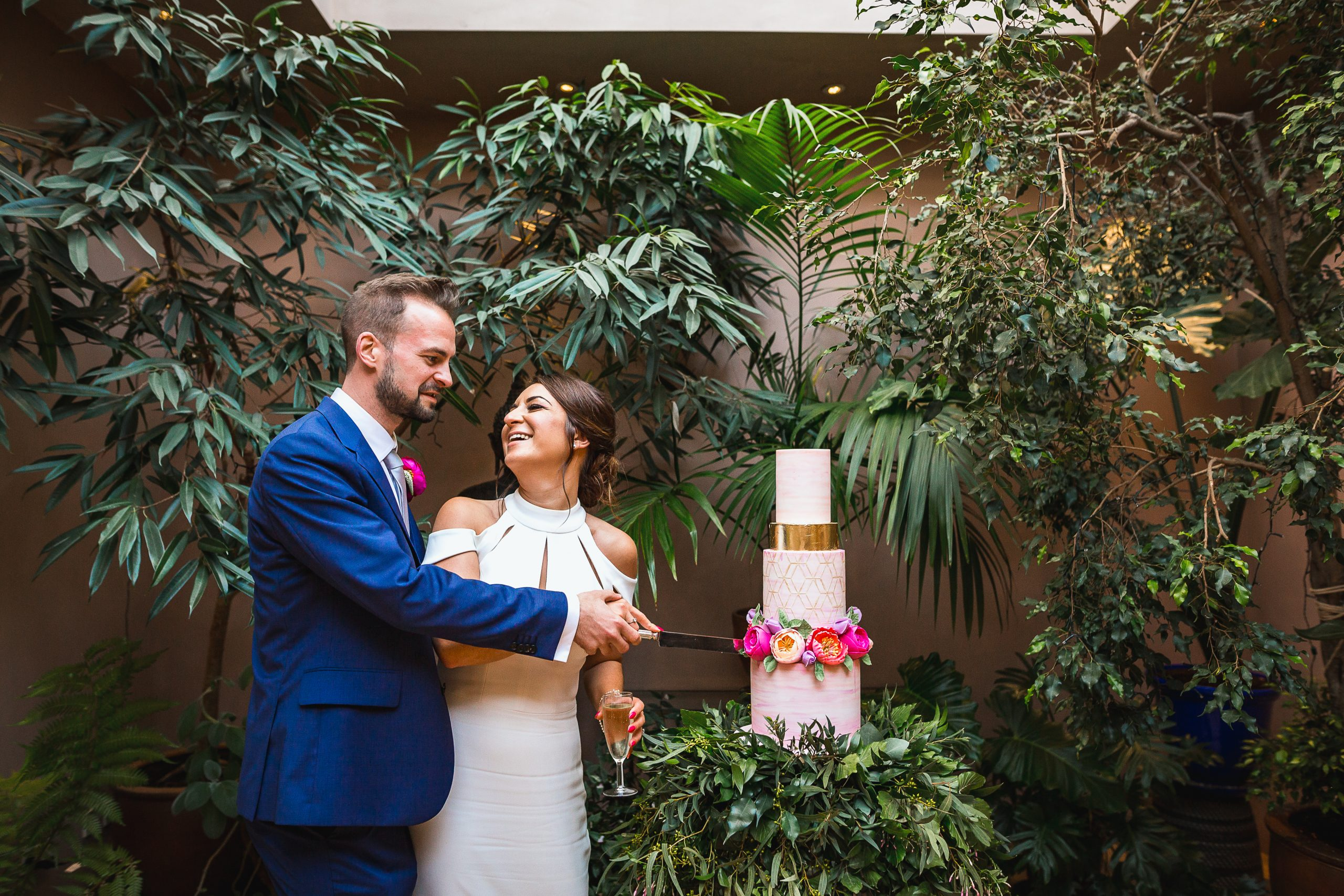 bride and groom beside white pink and gold wedding cake on a bed of cascading foliage